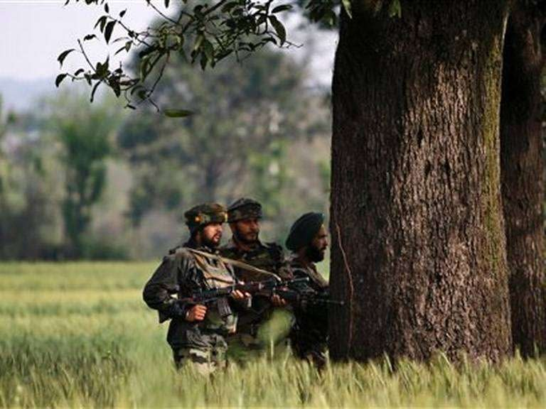 Indian army soldiers take position behind a tree